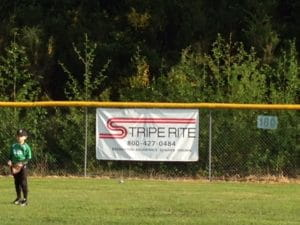 A Stripe Rite sign on the Gig Harbor Little League outfield fence