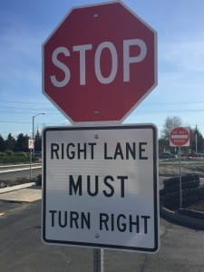 "A stop sign & ""right lane must turn right"" sign at the Stryker business center parking lot in Kent"