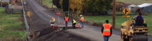 A Stripe Rite crew patches asphalt on a road