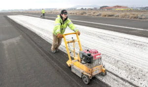 A Stripe Rite crew removes pavement markings using a grinder